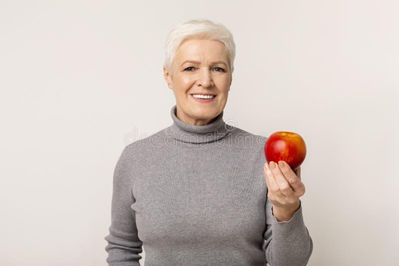 Slachende oudere vrouw met rode appel boven de achtergrond van een lichtstudio royalty-vrije stock afbeelding