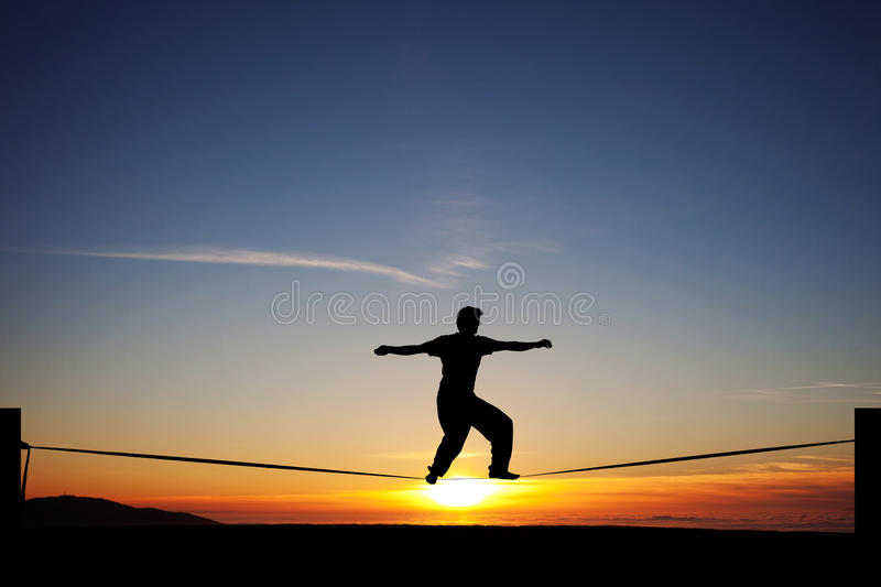 Slackliner in sunset. Silhouette of man slacklining in sunset royalty free stock images