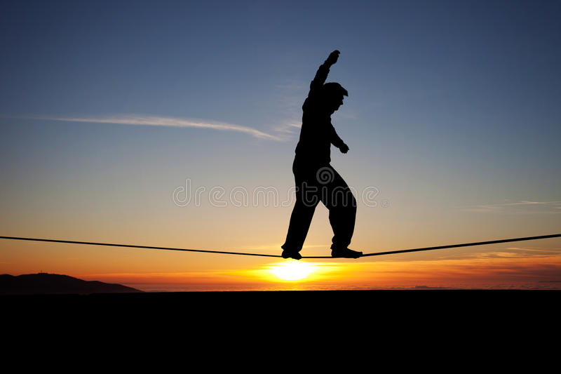 Slackliner in sunset. Silhouette of man slacklining in sunset royalty free stock photos