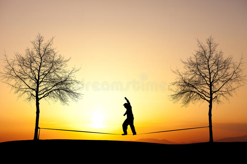Slackliner in sunset. Silhouette of man slacklining in sunset stock photography