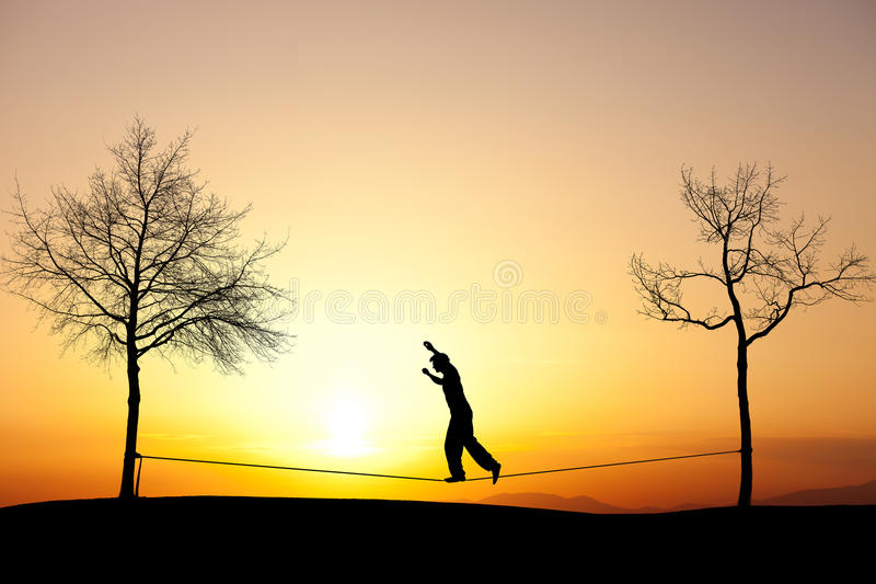 Slackliner in sunset. Silhouette of man slacklining in sunset stock photo