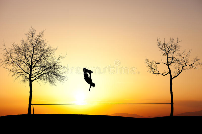 Slackliner in sunset. Silhouette of man slacklining in sunset royalty free stock photography