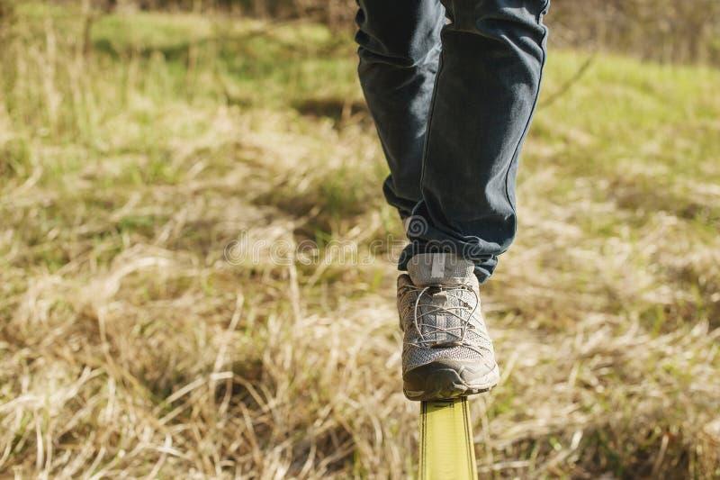 Slacklining is een praktijk van het in evenwicht brengen, waarin nylon of polyester de stof tussen twee ankerpunten dat is wordt  stock foto's