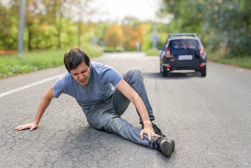 Slag- och körningsbegrepp Sårad man på vägen framme av en bil royaltyfria foton