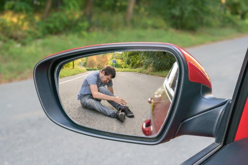 Slag- och körningsbegrepp Sikt på sårad man på vägen i bakre spegel av en bil arkivfoto