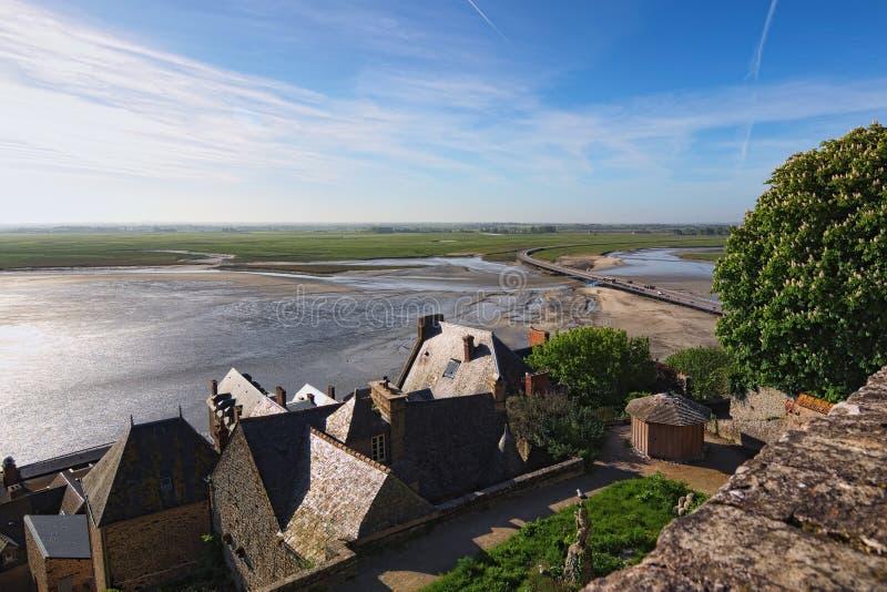 Slag tussen water en land Het vloedwater gaat naar de brug tussen Mont Saint-Michel-abdij en land royalty-vrije stock afbeelding