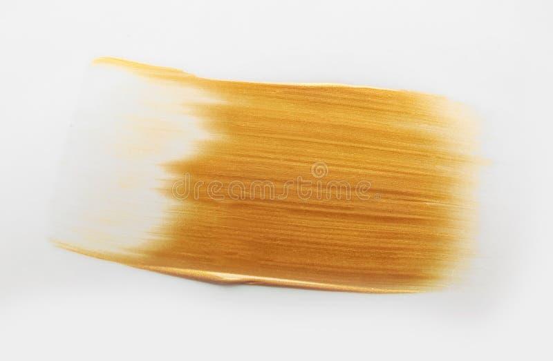 Slag van gouden verf op wit royalty-vrije stock foto