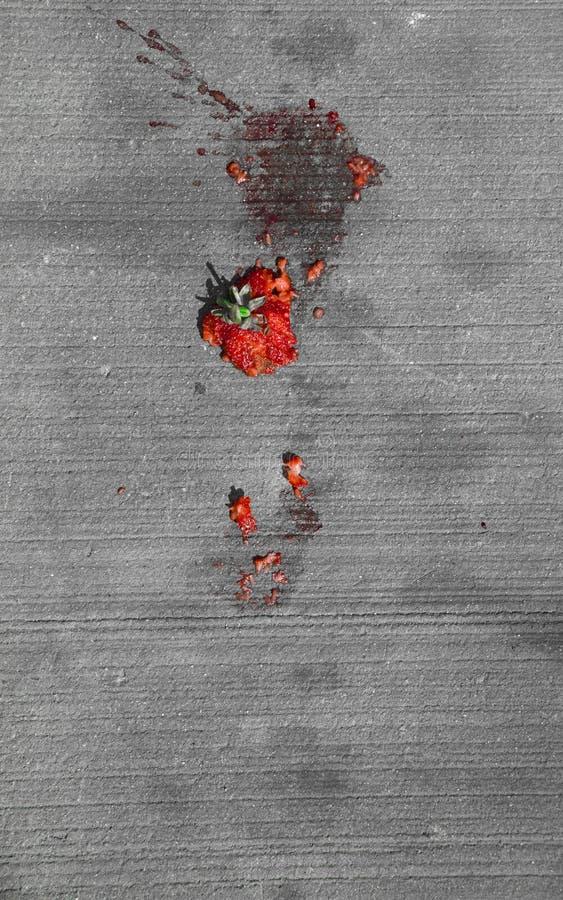 Slagen röd jordgubbe på trottoaren arkivbild