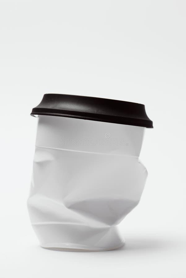 Slagen vit plast- kopp med locket royaltyfri foto