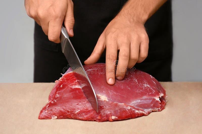 Slager die vers ruw vlees op teller in winkel snijden stock foto