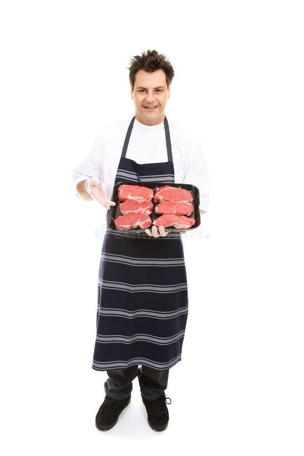 Slager die vleesbesnoeiingen voorstelt stock foto