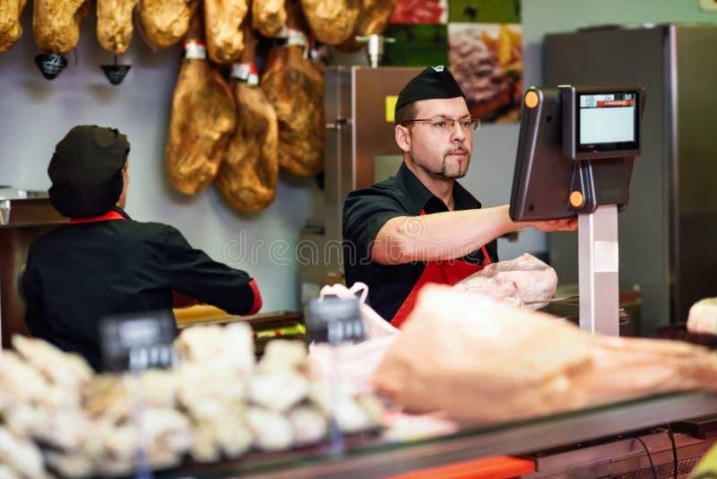 Slager in een slagers` s winkel die het vlees en het laden wegen stock afbeelding