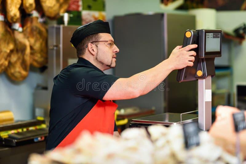 Slager in een slagers` s winkel die het vlees en het laden wegen stock foto