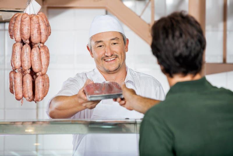Slager Giving Packed Sausages aan Klant royalty-vrije stock afbeeldingen
