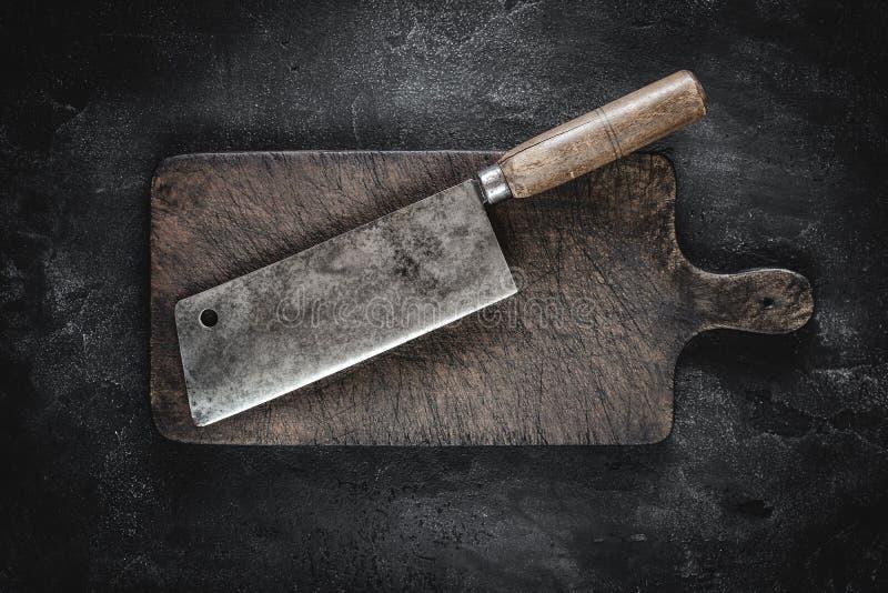 Slager Meat Cleaver en Rustiek Houten Hakbord op Donkere Achtergrond royalty-vrije stock fotografie