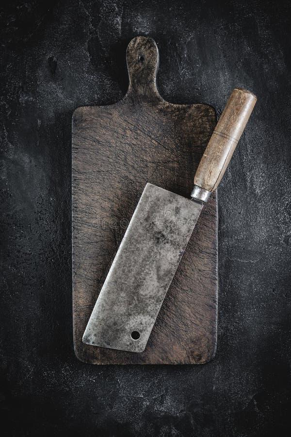 Slager Meat Cleaver en Rustiek Houten Hakbord op Donkere Achtergrond royalty-vrije stock afbeelding