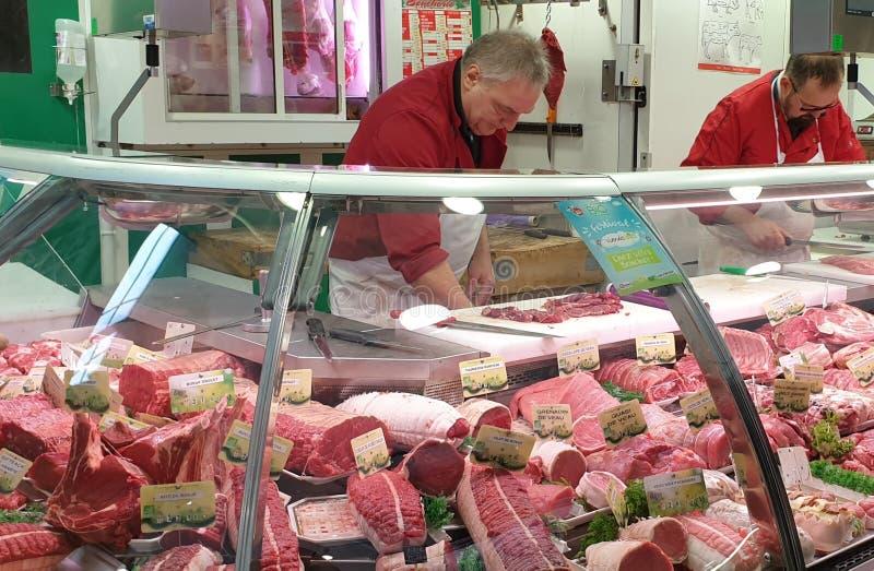 Slagers achter de teller bij de vleesmarkt in Nantes, Frankrijk royalty-vrije stock fotografie
