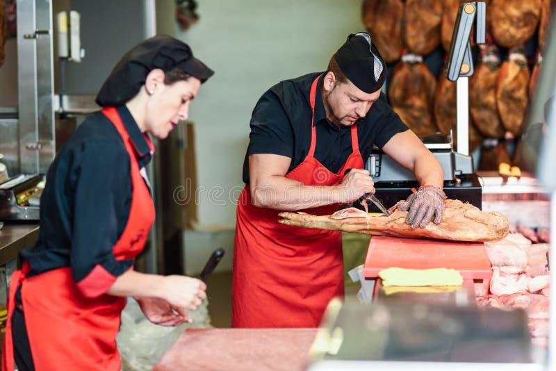 Slagers die een ham in een moderne slagerij uitbenen stock afbeeldingen