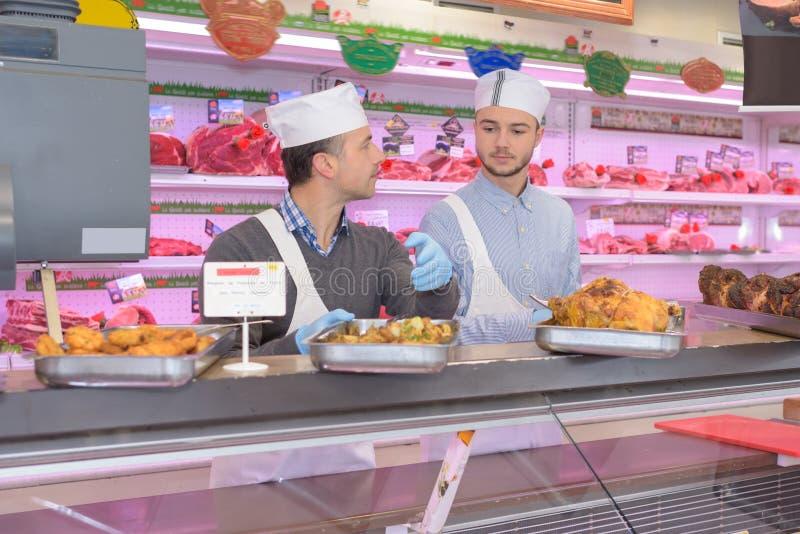 Slagers die zich achter teller in supermarkt bevinden royalty-vrije stock fotografie