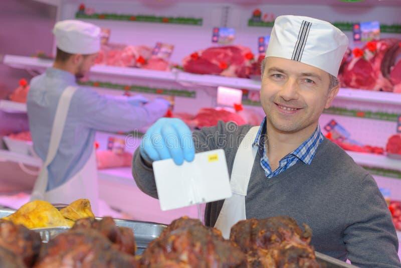 Slagers onderwijzende jongelui één hoe te om vlees te verkopen royalty-vrije stock foto