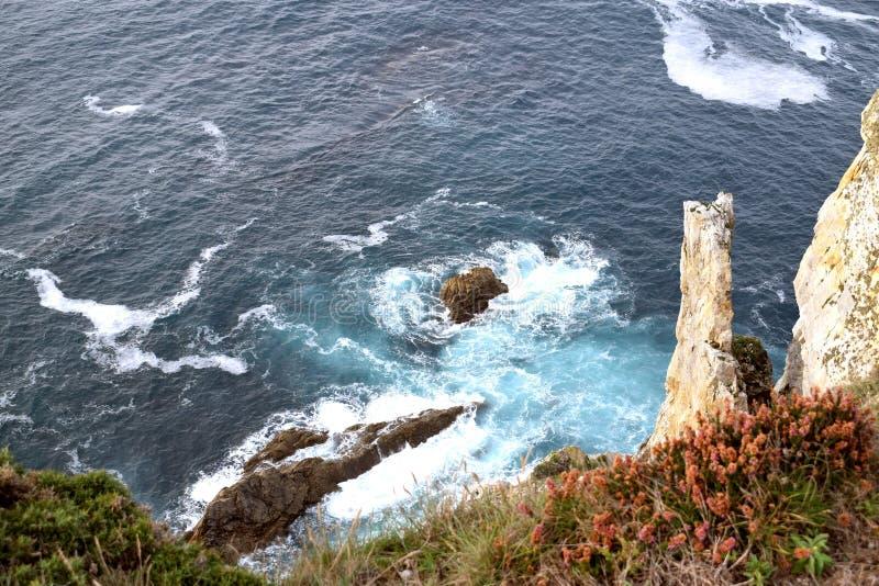 Slagfärg av havvågor mot vaggar royaltyfri foto