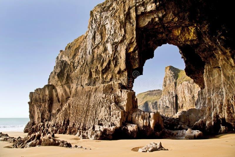 Slaggat die een rotsoverwelfde galerij onder Pembroke Coastline tussen Lydstep en Manorbier-Baai vormen stock afbeeldingen