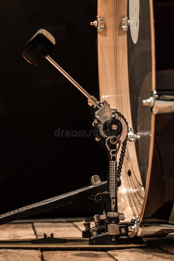 slaginstrument, bastrommel met pedaal op houten raad met een zwarte achtergrond stock afbeeldingen