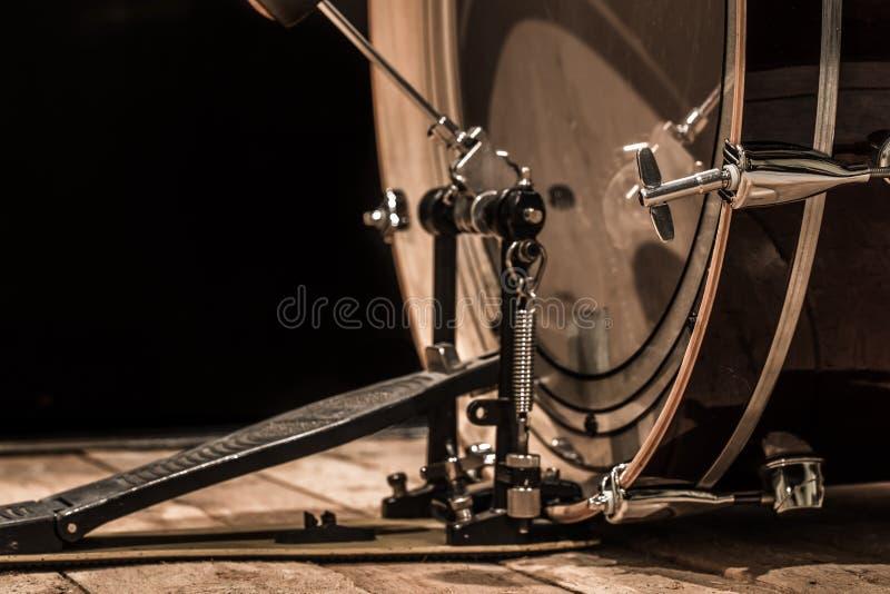 slaginstrument, bastrommel met pedaal op houten raad met een zwarte achtergrond royalty-vrije stock foto