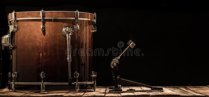 slaginstrument, bastrommel met pedaal op houten raad met een zwarte achtergrond stock foto's