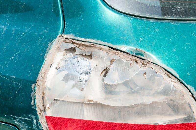 Slagit och skadat bakre stoppljus på den gröna bilen som är bruten vid vandaler eller i forcerat olycksslut upp royaltyfria bilder