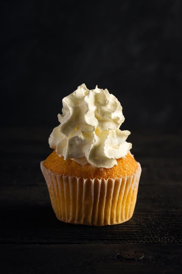 Slagroom cupcake op een donkere achtergrond royalty-vrije stock afbeeldingen