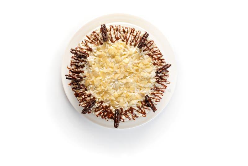 Slagroomcake die met amandelspaanders en chocolade wordt verfraaid op geïsoleerde witte achtergrond stock afbeelding