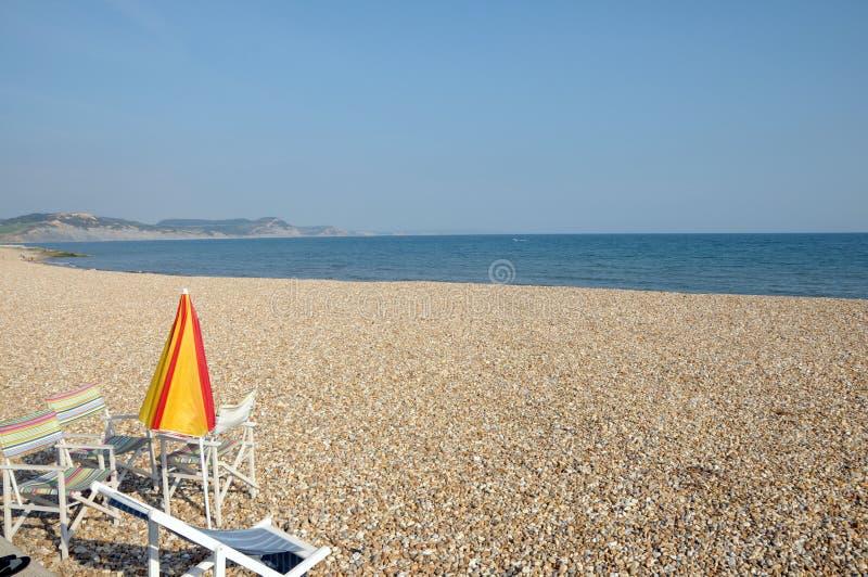 Slags solskydd och tabell på Lyme Regis, Dorset royaltyfri foto