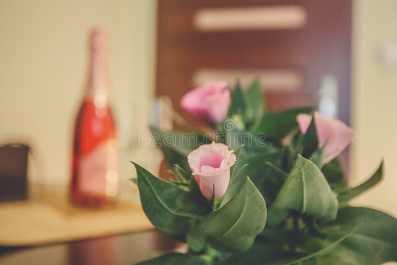 Slags tvåsittssoffa och romantisk säng med rosa kronblad Vit sängkläder, blommor, champagneflöjter arkivbilder