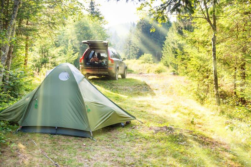 Slags tvåsittssoffa som campar med tältet och en bil royaltyfri foto