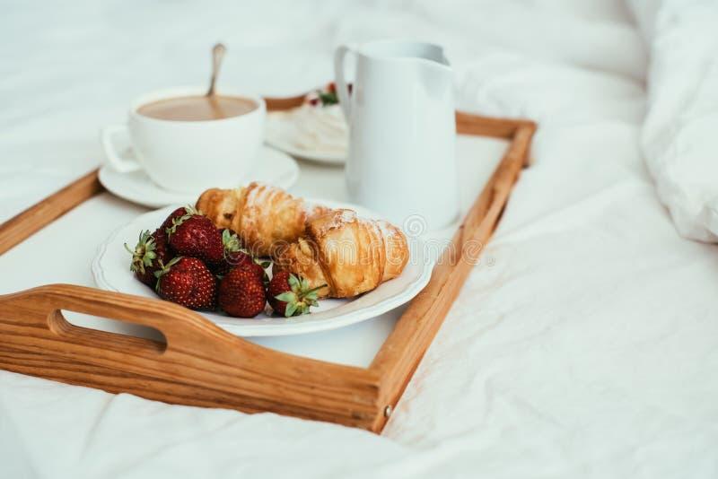 Slags tvåsittssoffahemfrukost i säng i den vita sovruminre royaltyfri fotografi