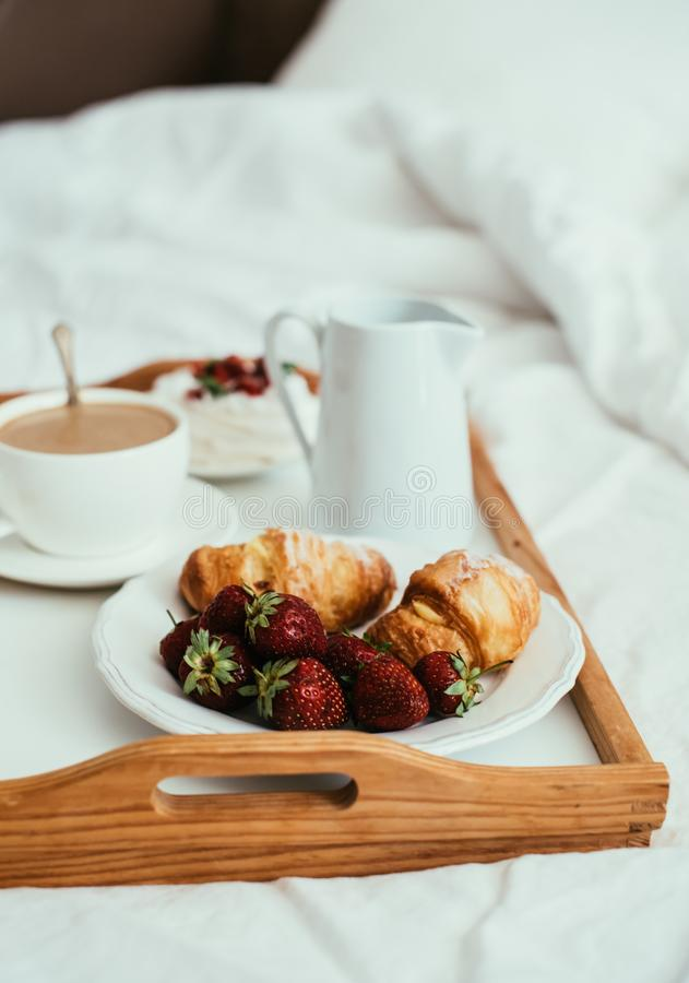 Slags tvåsittssoffahemfrukost i säng i den vita sovruminre royaltyfri foto