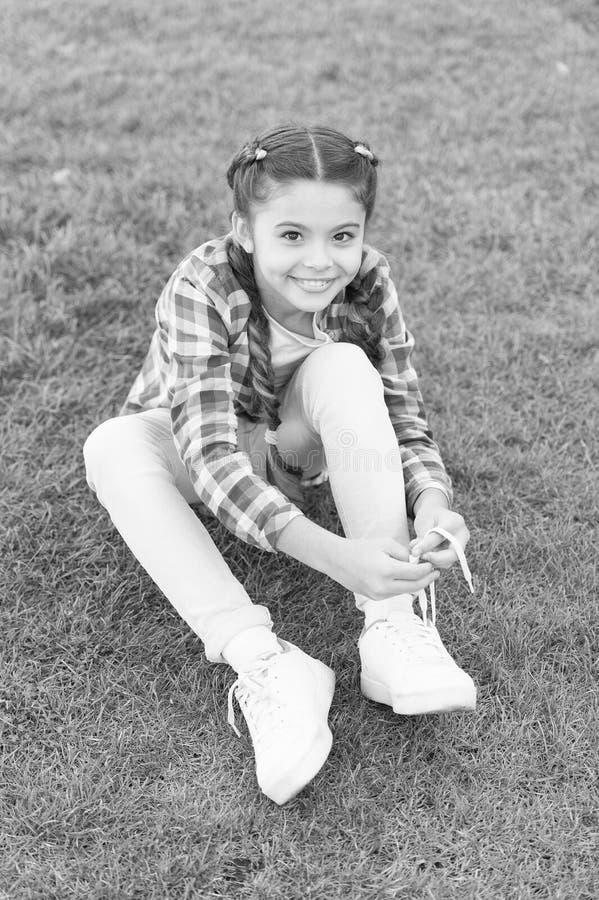 Slagschoenen Meisjes, kleine jongen brengen vrijetijdsbesteding in het park door Het meisje zit op gras in het park Kind geniet v royalty-vrije stock afbeeldingen