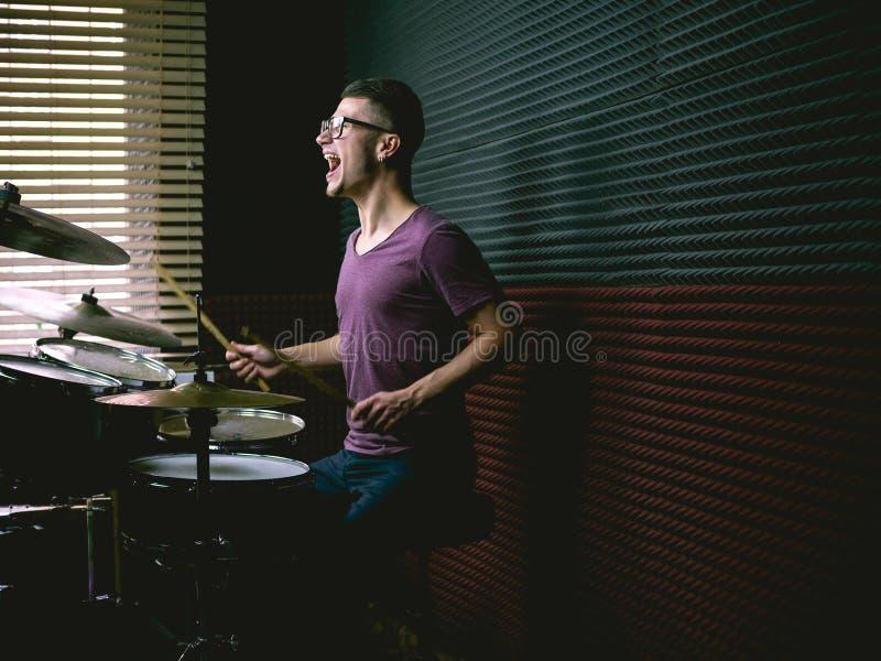 Slagwerker in muziekstudio het spelen trommels stock afbeelding