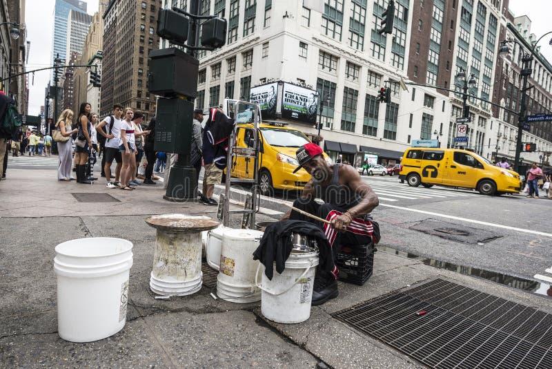 Slagwerkermens het spelen van plastic potten zoals een trommel op Zevende Weg 7de Weg met mensen royalty-vrije stock foto