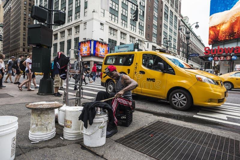 Slagwerkermens het spelen van plastic potten zoals een trommel op Zevende Weg 7de Weg met reusachtig royalty-vrije stock afbeelding