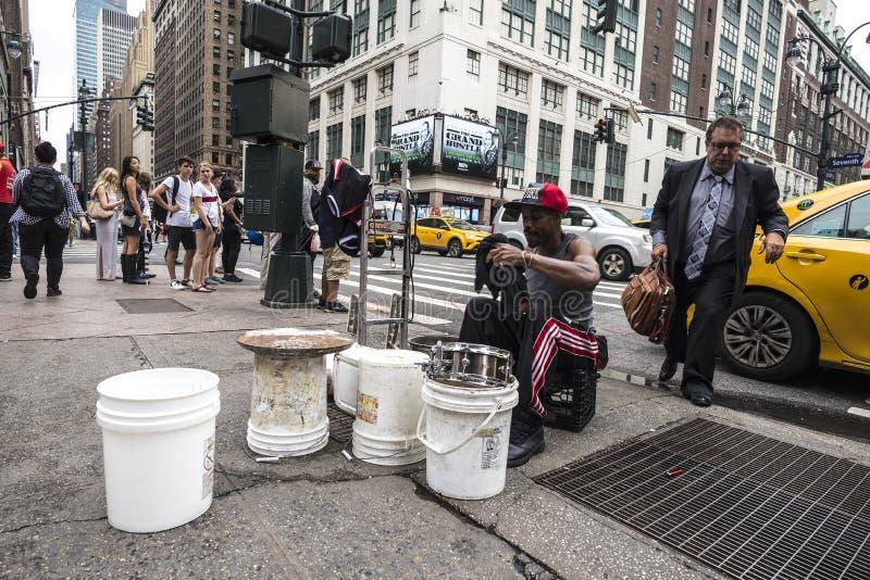 Slagwerkermens het spelen van plastic potten zoals een trommel op Zevende Weg 7de Weg terwijl een mens stock fotografie