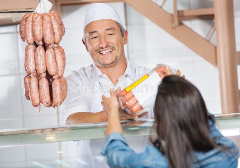 Slaktare Giving Packed Sausages till den kvinnliga kunden fotografering för bildbyråer