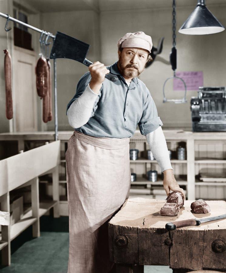 Slaktare som hugger av kött med köttyxan (alla visade personer inte är längre uppehälle, och inget gods finns Leverantörgarantier royaltyfri foto