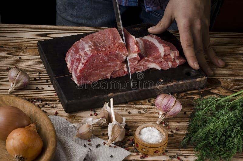 Slaktare som klipper griskött på träbräde på en trätabell på den mörka bakgrunden royaltyfria foton