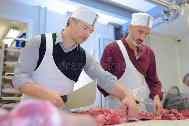 Slaktare som klipper nytt kött i skinka- och grisköttfabrik fotografering för bildbyråer