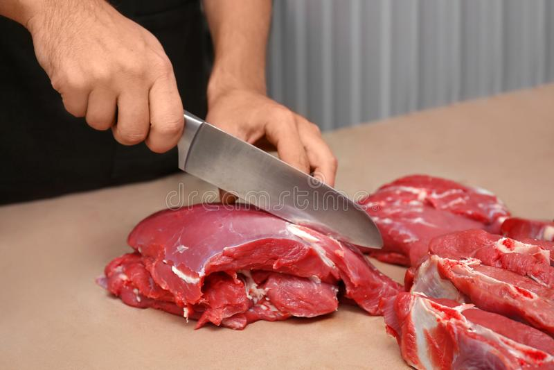 Slaktare som klipper nytt rått kött royaltyfri foto