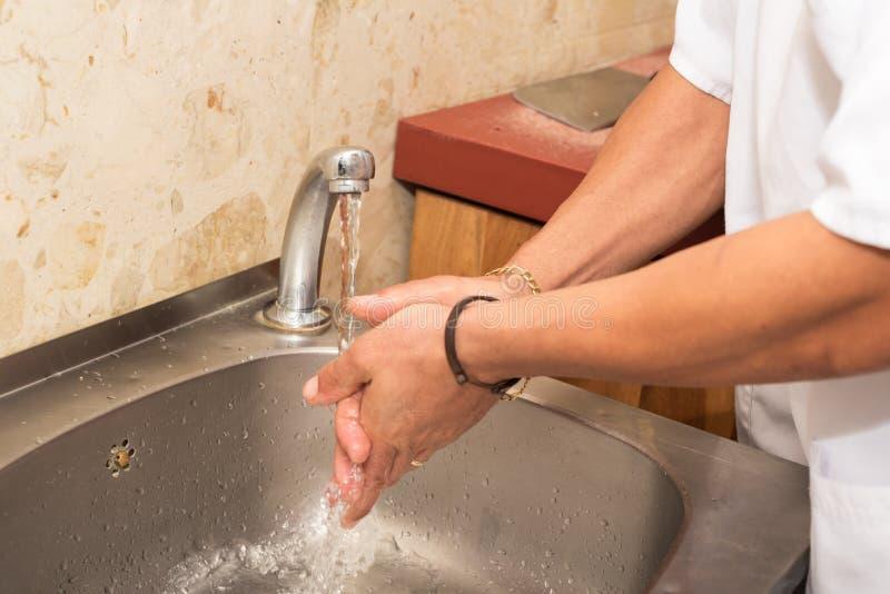 Slaktare som tvättar hans händer royaltyfri foto