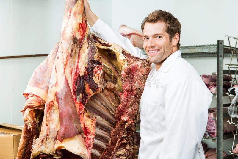 Slaktare Standing Beside Beef i kylare royaltyfri fotografi