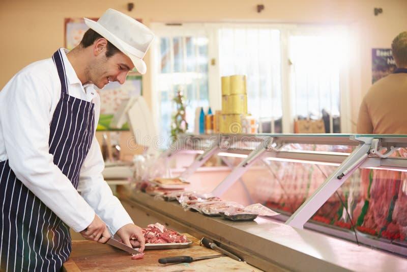 Slaktaren Preparing Meat In shoppar arkivbilder